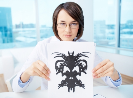 clinical psychology: Serious psychologist showing paper with Rorschach inkblot Stock Photo