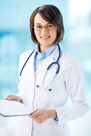 general practitioner: Vertical portrait of a lovely general practitioner holding document