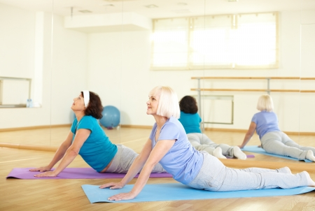 Portrait of sporty females doing stretching exercise in sport club photo