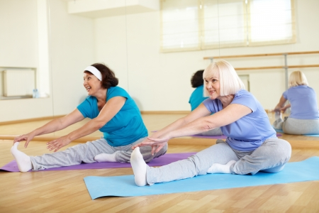 Portrait of sporty mature females doing stretching exercise in sport club photo