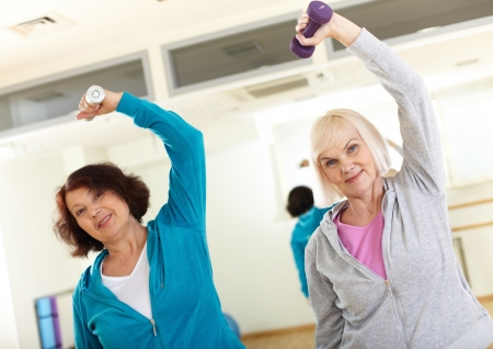elderly exercise: Portrait of sporty females doing physical exercise with barbells in sport gym