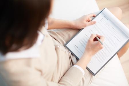 terapia psicologica: Consejero Mujer escribiendo una cierta informaci�n sobre su paciente