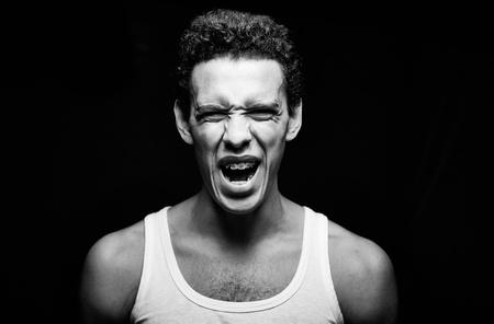 man screaming: Portrait of handsome guy in vest screaming
