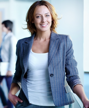 on the foreground: Image of pretty businesswoman looking at camera