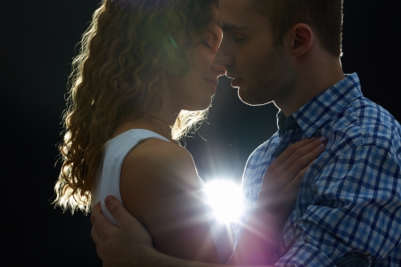 Young couple kissing in the dark