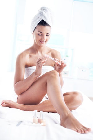 Girl with a towel on her head and body taking care of her fingernails Stock Photo