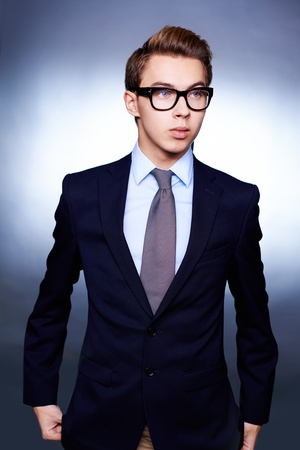 Vertical portrait of a handsome businessman in suit and eyeglasses photo