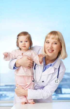 Vertical portrait of a lovely pediatrician holding baby and both looking at camera photo