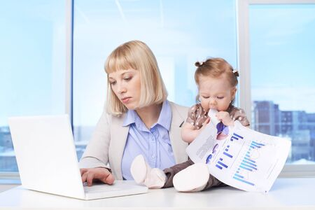 Confident businesswoman typing at workplace with her baby tasting document near by photo