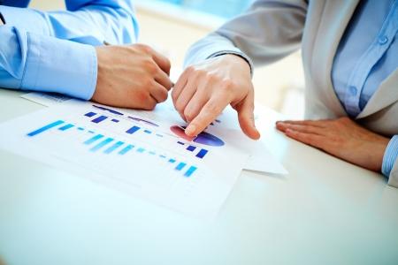 recursos financieros: Primer plano de la mano femenina que señala en el documento de negocio en el entorno de trabajo