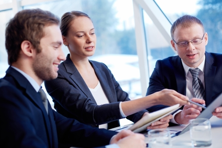 group business: Group of confident business partners discussing paper at meeting