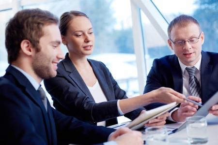 reunion de personas: Grupo de socios de negocios confiados en discusiones papel a satisfacer