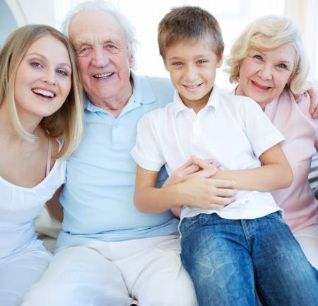 mujeres mayores: Retrato de pareja de ancianos con su hija y su nieto mirando la c�mara en casa
