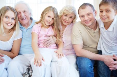 mujeres mayores: Retrato de matrimonios mayores y j�venes con sus hijos mirando la c�mara en casa