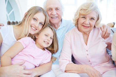 Portrait of senior couple with their daughter and granddaughter looking at camera photo