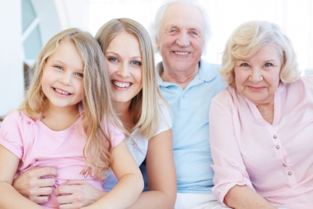 grandmother and children: Portrait of senior couple with their daughter and granddaughter looking at camera Stock Photo
