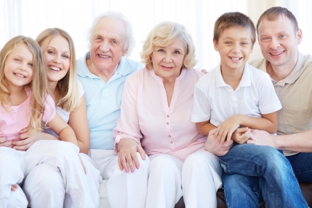 grandmother and children: Portrait of senior and young couples with their children looking at camera at home