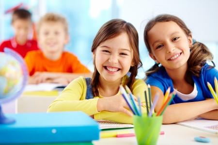 Portrait de deux jeunes filles assidus regardant la caméra au lieu de travail avec des écoliers en arrière-plan
