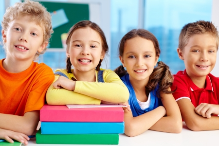 diligent: Group of diligent schoolchildren looking at camera in school Stock Photo