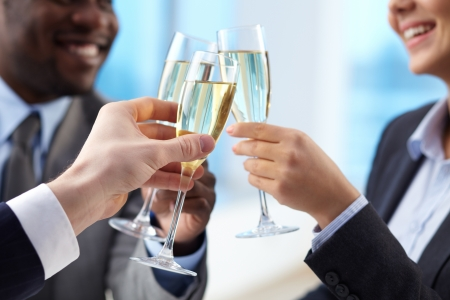 corporate woman: Close-up of business partners hands cheering up with flutes of golden champagne Stock Photo