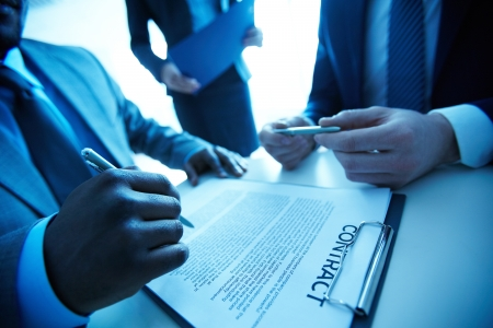decision making: Image of contract on workplace and group of partners making decision to sign it Stock Photo