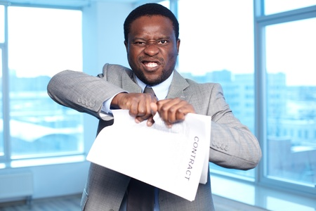 Portrait of angry African businessman tearing contract and looking at camera Stock Photo - 18310091