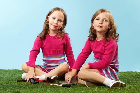 niñas gemelas: Retrato de dos chicas inteligentes en ropa elegante que se sienta en el césped y mirando a la cámara Foto de archivo