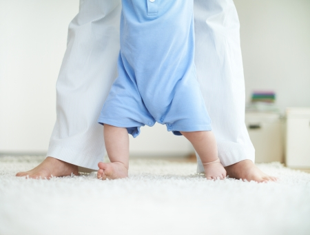 toddler walking: Close-up of female and little baby legs during walk down the floor
