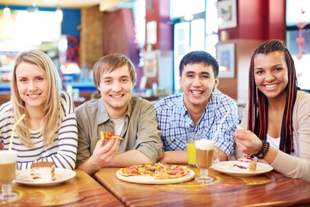 Image of teenage friends enjoying themselves in cafe photo