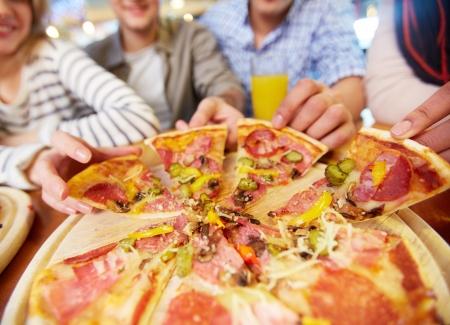 hombre comiendo: Imagen de manos de amigos adolescentes que toman porciones de pizza