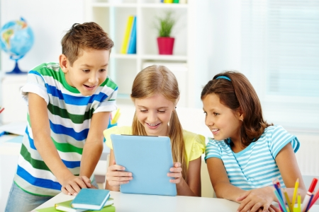 wow: Portrait of happy classmates at workplace using digital tablet