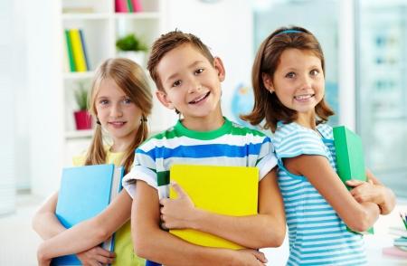 niños estudiando: Retrato de los compa?eros felices con los libros que mira la c?mara en el aula