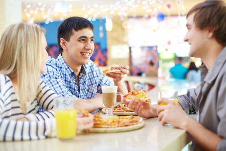 Image of teenage friends interacting in cafe photo