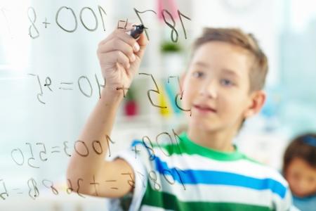 matematica: Estudiante lindo haciendo sumas con colegio en el fondo