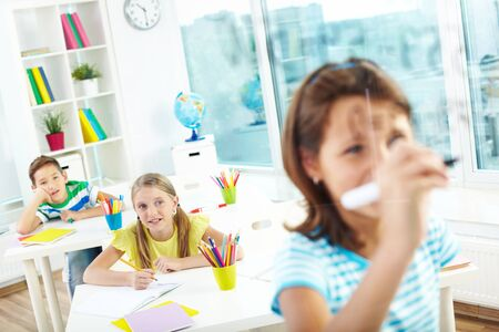 arithmetic: Schoolgirl doing sums on transparent board with two schoolmates looking at her Stock Photo