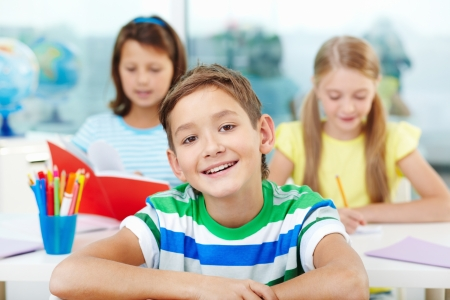 primary school: Portrait of smart lad at workplace looking at camera with two classmates on background