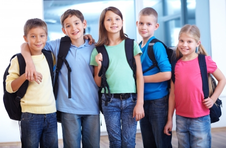 Portrait of smart schoolkids standing in line and looking at camera
