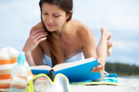 Image of pretty female lying on the beach and reading book photo