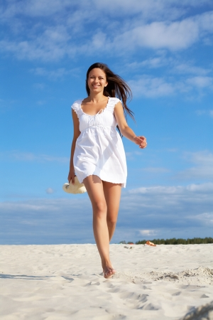 Image of female in white dress walking down sandy beach photo