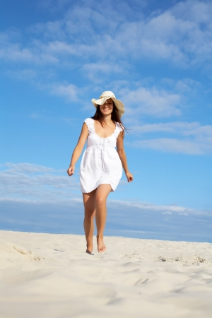 Image of female in white dress and hat walking down sandy beach Stock Photo - 18457657