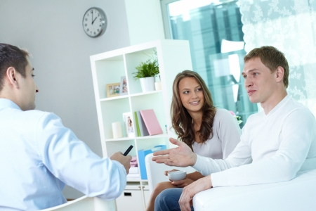 Young couple discussing their actuarial plan with an insurance broker photo