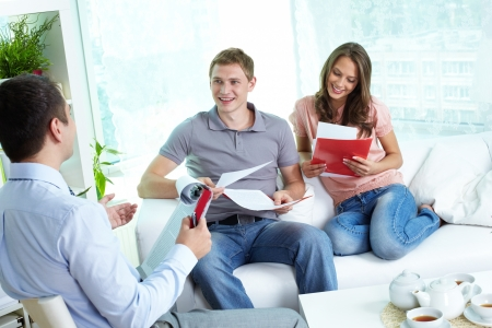 insurance consultant: Young family reading insurance contract, their agent advising
