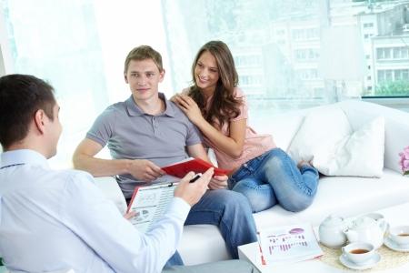 agente comercial: Pareja joven discutiendo su estrategia de inversión con un asesor financiero