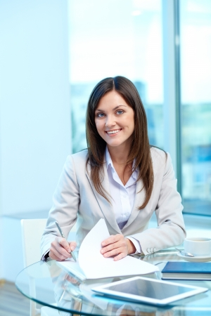 proficiency: Portrait of young female looking at camera while checking proficiency test Stock Photo