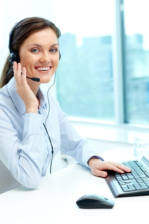 Portrait of young operator with headset looking at camera with friendly smile Stock Photo - 18591661