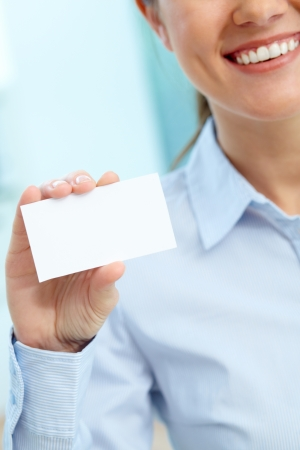 Close-up of blank card shown by a lovely young businesswoman photo