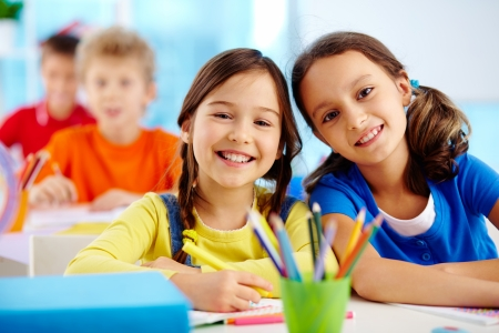 diligent: Portrait of two diligent girls looking at camera at workplace with schoolboys on background
