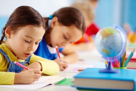 niños estudiando: Los alumnos se sientan en una fila escribir un ensayo Foto de archivo