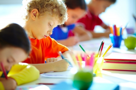 kids learning: Portrait of cute schoolboy drawing at workplace among his classmates