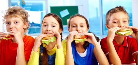 ni�os comiendo: Cuatro colegiales mirando a la c�mara mientras almorzaba durante las vacaciones